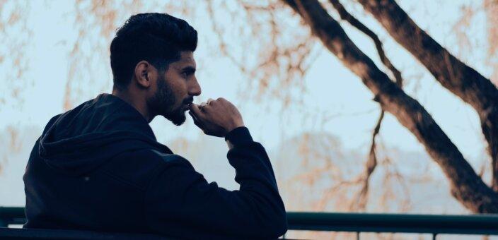 man-in-black-hoodie-sitting-on-bench-near-green-trees-819635